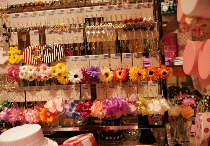 Mini top hats and bright flower accessories, Harajuku girls fashion, anchor earrings and fake flower gold hoops. Marui One department store in Shinjuku, Tokyo, Japan. Where to buy cool designer jewelry in Japan, Tokyo best places for shopping.