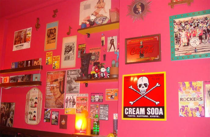 Rockabilly curry house, 1980s restaurant interior decoration, pink walls, vinyl records on walls, Beatles sgt pepper album cover, cream soda skull crossbones sign, Koenji bars and clubs, Japanese otaku cafes, nakano Broadway mall, anime manga cosplay stores, Tokyo Japan cool cafe.