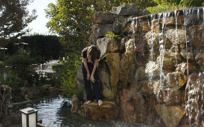 man made stone waterfall, Japan Buddhist temple stone garden pond, boy underneath waterfall, Buddhism meditation photos, Kyoto Grand hotel in Los Angeles, Zen garden, meditation pond, Japanese park and gardens in LA