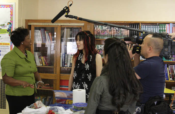 reporter interviewing school principal, tv cameras and audio boom microphone, pretty japanese girl models, Asian tv stars, young Japan Chinese girls, black skull scarf, silk black goth prom dress, TEACHING CHILDREN HEALTHY EATING HABITS, CUTE CHARACTER BENTO-MAKING AT HARLEM ELEMENTARY SCHOOL. pretty Asian model, Chinese idol girl, NHK TV, KAWAII BENTOS TV SHOW: LA CARMINA, BLOGGER & CUTE YUMMY TIME AUTHOR. filming japanese game show, charaben, CUTE CHARACTER BENTO, crazy FOOD COOKING SHOW, NHK JAPAN TV DOCUMENTARY SHOOT, NEW YORK WAVE